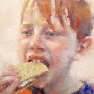 young boy taking a big bite of a smore